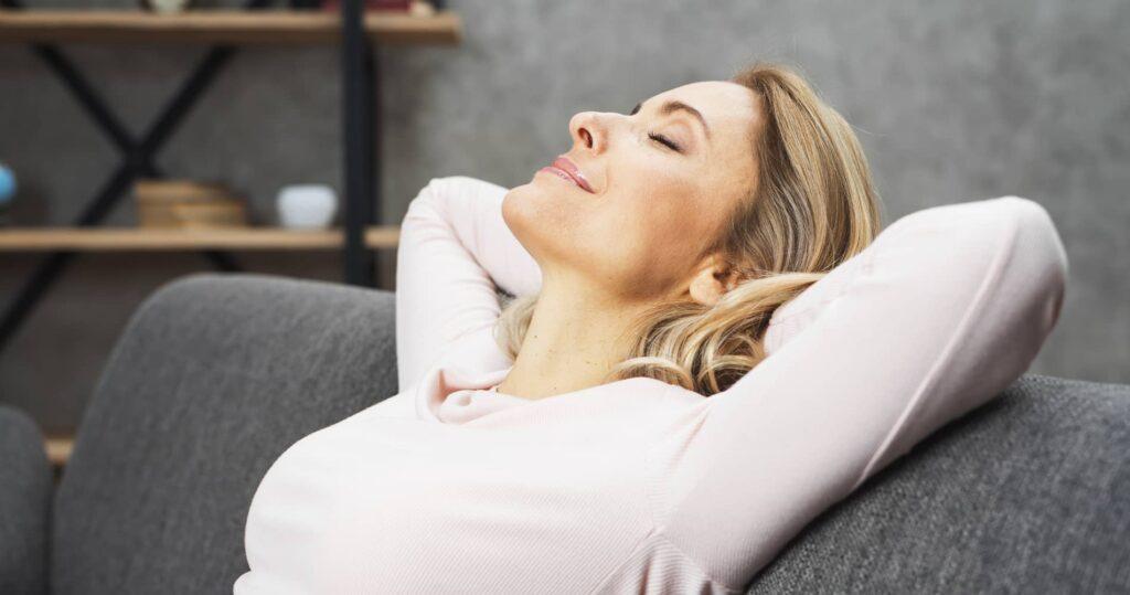 femme sur son canapé recevant séance de reiki